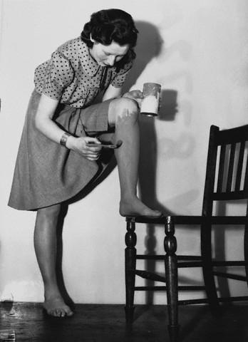 Британская женщина наносит на ноги жидкие чулки, 1940г.