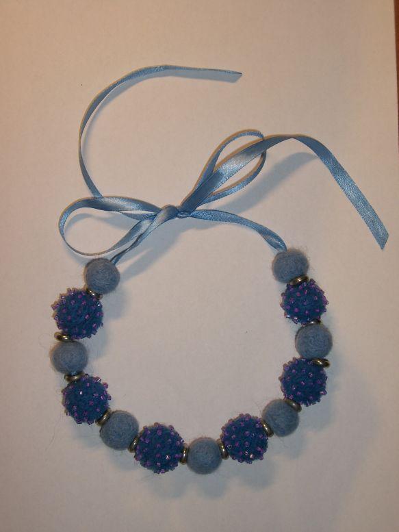 Валяные бусины синего и голубого цветов, расшитые сиреневым бисером; металлическая фурнирура; атласная лента.