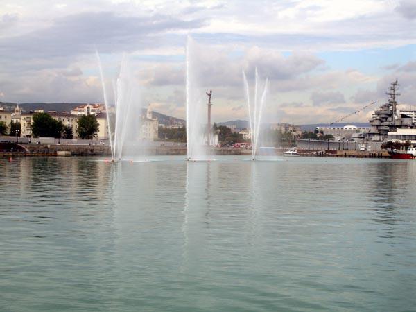 Фонтаны, а взади новый постамент фонтан в виде крылатой девушке, которая держит кораблик...
